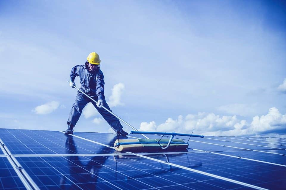 Technician cleaning rooftop solar panels
