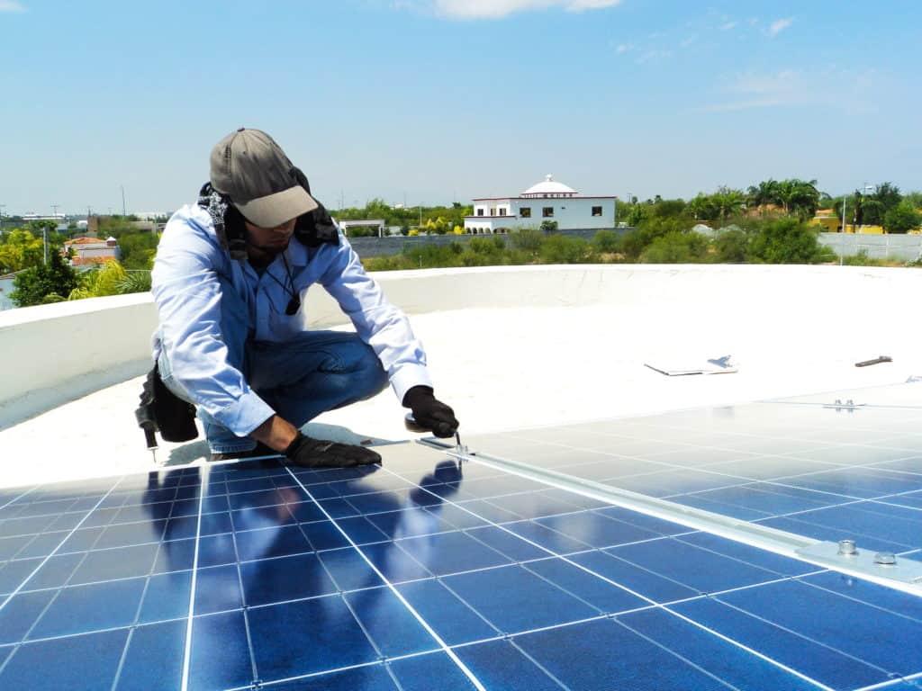 A photo of a man repairing a solar panel
