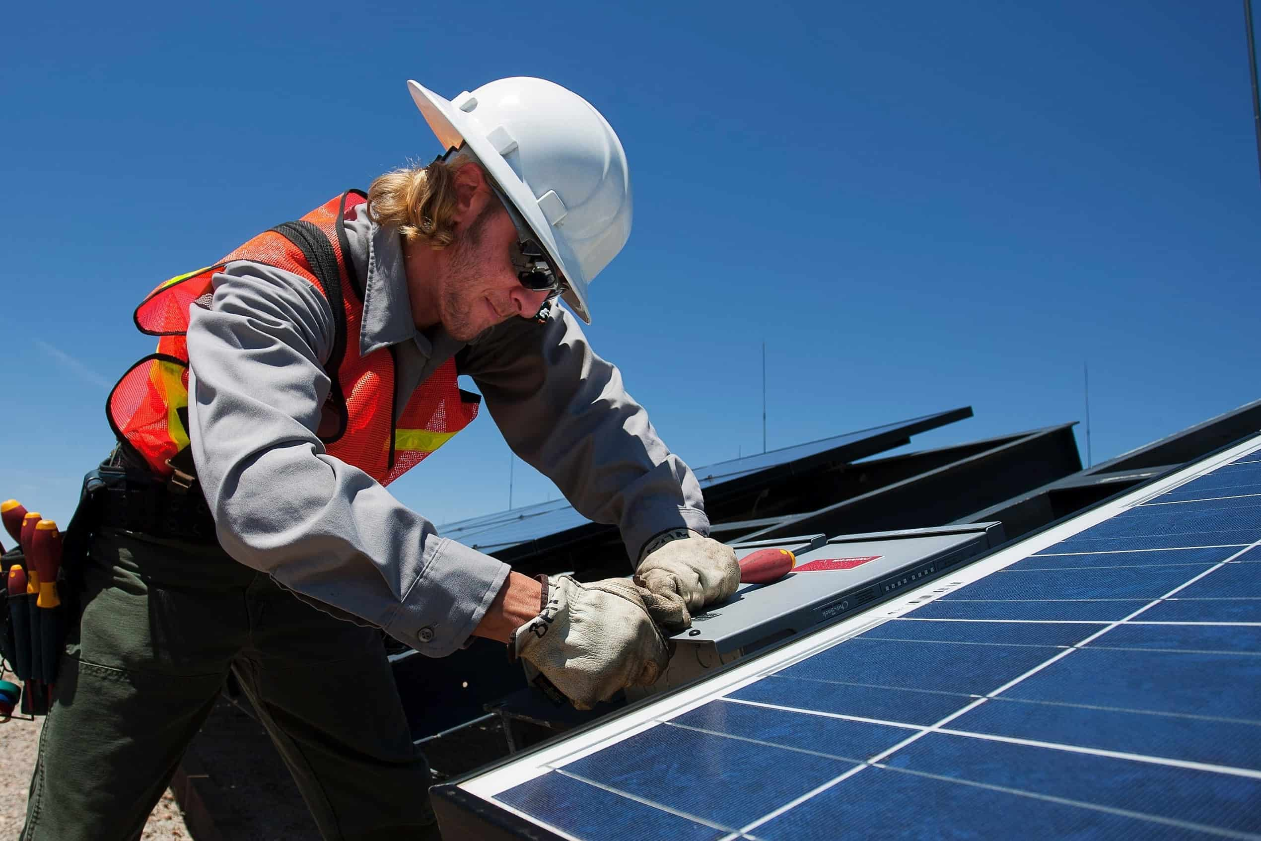Photo of a man maintaining a solar panel